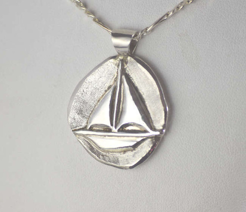 The sterling silver sailboat pendant is handcrafted in Portland, Maine.  The pendant has a sailboat carved on the front of the pendant and it weighs 10.7 grams.  The pendant is solid and measures 32 mm. x 24 mm. x  3 mm. and the bail fits 3.5 mm. chain.