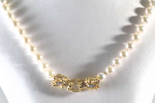 The pearl strand is an 18 Inch Japanese akoya strand.  The pearls are 7.5 mm. - 8 mm. with a AA quality and are knotted in between each pearl.  There is a 14 K yellow gold double dragon head clasp.  The clasp has .28 carats of diamonds with a color of J and a clarity of I1 and there are four 1 mm. round rubies for eyes.  The clasp is a hand made clasp and very unique.
