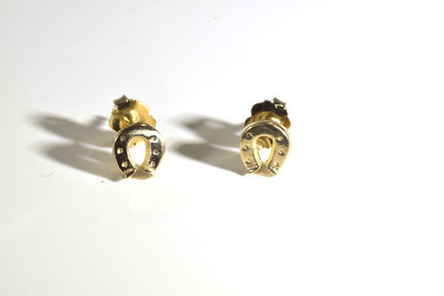 The tiny gold horse shoe studs are  hand crafted in Portland, Maine.  The horse shoe was carved and cast measuring 1/4 x 1/4 x 1/16 inch and weigh 1.7 grams.  The studs have a polished finish and are solid. The earrings  3/8 x 5/16  x 3/8 inch. The earrings are 14 K yellow gold.