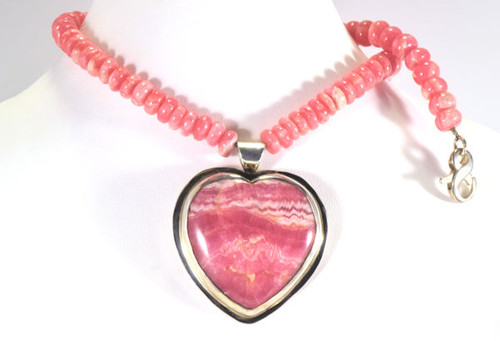 The rhodocrosite heart necklace is hand crafted in Portland, Maine.  The heart is a rhodocrosite from Argentina and is set in a sterling silver bezel pendant.  The pendant is on a 8 mm. button shaped bead strand with a sterling silver lobster claw clasp.  The necklace weighs 68.4 grams and is 16.5 inches in length.
