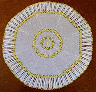 Octagonal crocheted baby shawl featuring rings of daisy chains.