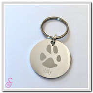 A single dog paw print on a stainless steel keychain