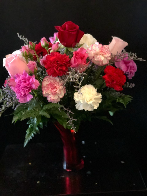 Tired of the same old thing?  Let us send a beautiful mixture of carnations, roses and spray roses in a gorgeous red flared vase to you your Valentine