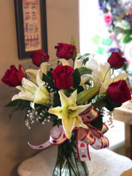 Red roses, Lilies and Babies Breath arranged just for you and accented with a bow