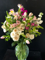 An arrangement of airy and subtle roses, alstromeria, stock, tulips, etc that give you the feeling you are outside an English cottage in the spring.