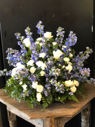 Always looking for that Blue and White Spray?  Well, here it is.  Gorgeous layers of blue delphinium mingle with white roses and white carnations, creating a blue sky effect.  Can be done as a spray or fully round for a centerpiece.  Approximate size 28 x 24.