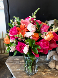Luxurious concoction in oranges and pinks featuring 18 hot pink roses, lisianthus, snap dragons and gerber daisies in our heavy cut glass aqua luxe line vase