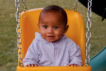 smiling baby enjoying baby swing accessory