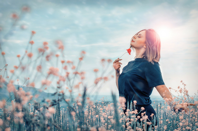 Woman placing flower to her chin, looking happy