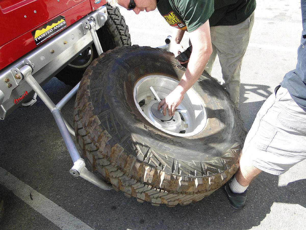 Thread on and tighten T-handle to press the tire up against the carrier cage.