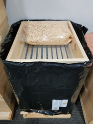 Quilt Box shown w/ pine shavings on a hive that's wrapped with a Bee Cozy.