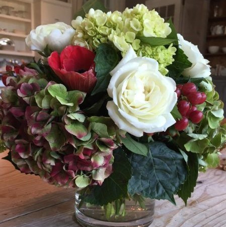Antique hydrangeas combine with white roses and red berries for a beautiful holiday gift.