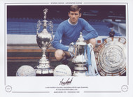 A proud Manchester City captain Tony Book poses with the League Championship, FA Cup & Charity Shield trophies in 1969.
