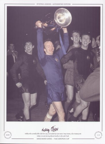 Nobby Stiles proudly holds aloft the cup, surrounded by team-mates Tonny Dunne, Alex Stepney and Paddy Crerand, after defeating Benfica in the 1968 Final.