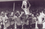 "Frank McLintock is chaired by team-mates after the 1971 FA Cup Final. The photograph is 12"" x 8"" (305mm x 205mm) and has been signed by Charlie George & Eddie Kelly."