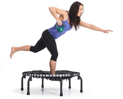 Lady balancing on one foot on a rebounder while holding a kettle ball in one hand and the other arm outstretched for balance