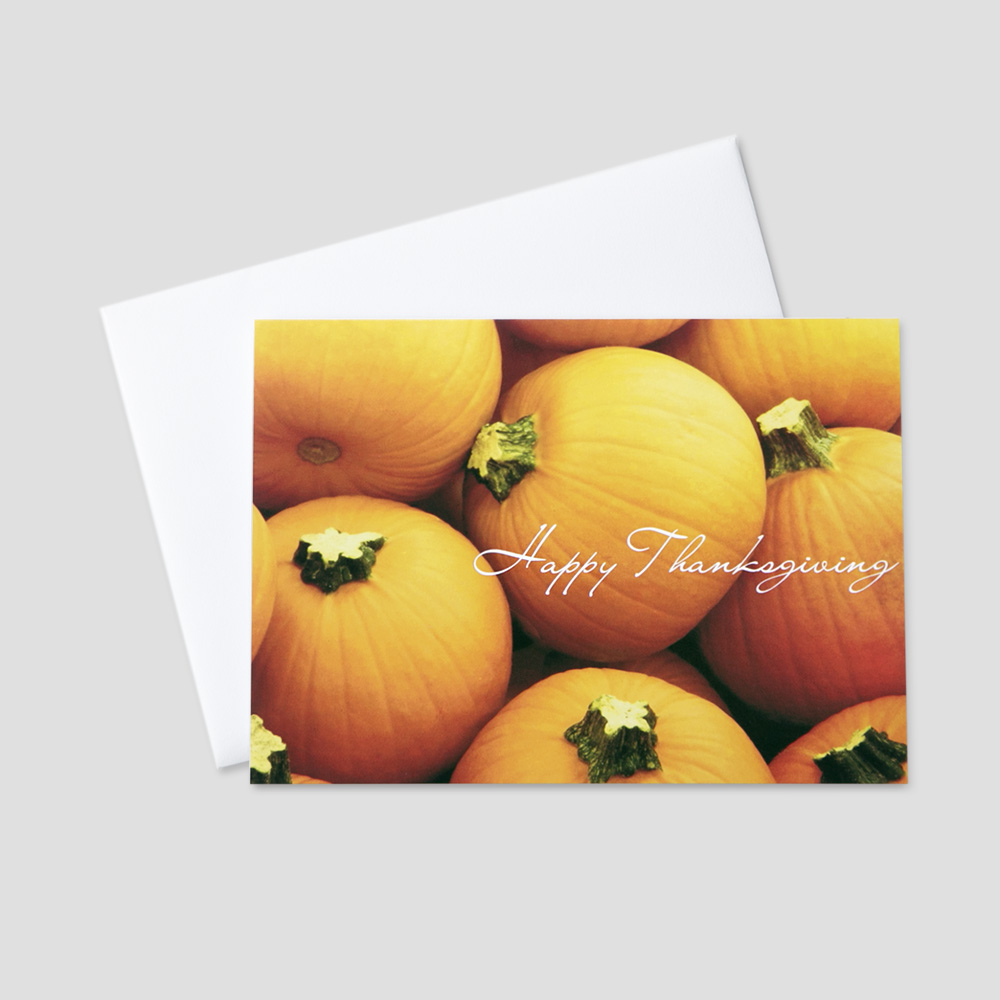 Professional Thanksgiving greeting card featuring a patch of bright orange pumpkins and Happy Thanksgiving in a white script font