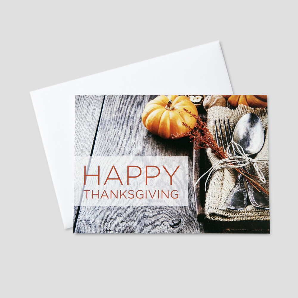 Company Thanksgiving greeting card featuring a small pumpkin and a thanksgiving place setting on a rustic wooden table