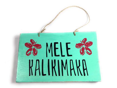 """Mele Kalikimaka"" Wooden Sign w/ plumeria design 8"" X 5"" | #snd25125"