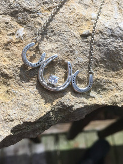 Trio of plate horse shoes in sterling with adjustable chain. Maximum length is 20 inches and adjusts with a silicon bead.  Comes with a cz. Can be done custom in  14K gold with any gemstone or your own gemstone
