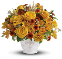 """Lush yellow roses, yellow alstroemeria, bronze button chrysanthemums and gold cushion chrysanthemums are arranged with greens including magnolia leaves, huckleberry, seeded eucalyptus, lemon leaf and natural wheat. Delivered in a charming French Country pot. Approximately 14 1/2"""" W x 13"""" H"""
