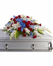 For a military or private funeral, this classic half-couch casket spray is a proud and patriotic way to pay lasting tribute to an loved one's esteemed memory, life of service and dedication to freedom. Bold flowers such as blue hydrangea and delphinium, classic red roses, and white oriental lilies and gladioli form an all-American display honoring the deceased and their love of country.