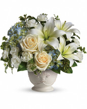 This French country style sympathy arrangement communicates your condolences in a most heartfelt way. It's a lovely choice when you want to send flowers to family or friends. A beautiful bouquet of blue and white sympathy flowers - blue hydrangeas, crème roses, white miniature carnations, fragrant white asiatic lilies and green pitta negra - are delivered in a French Country Pot. Orientation: One-Sided