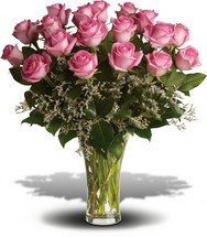 """Sending 18 perfectly pink roses and white limonium arranged in a glass vase to the woman you love shows that you know how much fun love is! And every woman appreciates that! Approximately 19"""" W x 21"""" H"""