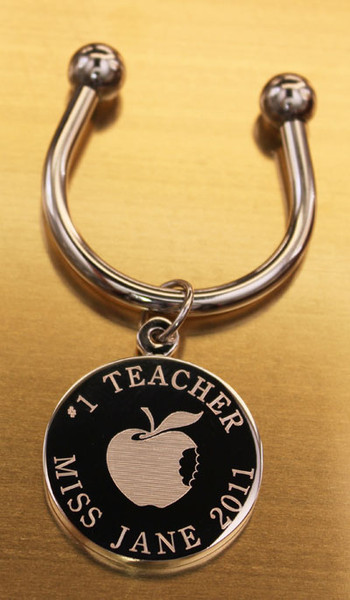 Teacher keychain.  Made of non tarnish high quality nickel plate.  Beautifully engraved round disk with apple graphic and text arched across the top and bottom.  Makes a great gift for teachers retiring or leaving the school.  The back of the round disk can be engraved up to 4 lines of text, which could include years of service.  Comes with horseshoe shaped keyring, round split ring keyring, engraved disk and boxed in a silver cotton filled gift box.