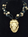 """#BN76 Be Daring. Be Unique. Bring Out the Animal in You!  This Fabulous Pendant of a Hand Made  Ceramic Gold Lion's Head on multi Strands of Gold and Black Beads will be Noticed!  Price $165.   Length 18"""" May be custom ordered to fit your needs for a slight extra charge."""