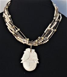 "#AN60 CARVED BEIGE FOSSIL STONE PENDANT HANGING FROM MULTIPLE STRANDS OF FOSSIL STONE AND GOLD BEADS $165. 18"" BUT MAY BE CUSTOM ORDERED IN A SIZE OF YOUR CHOICE."