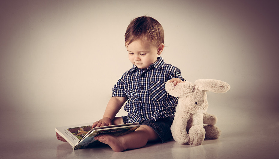 Adorable little boy reading a book and holding teddy in a photograph by Emotion Studios.