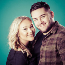 Photograph of young couple together in front of green background. Image by Emotion Studios photography.