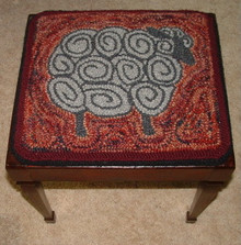 """Punch hooked by Angela Jones.  I made this into a square for a stool top.  The stool is an old """"Home Economics"""" stool you would sit on while learning to sew.  The top lifts off to store your sewing tools.  The sheep is natural color rug yarn and the background is hand dyed wool rug yarn."""