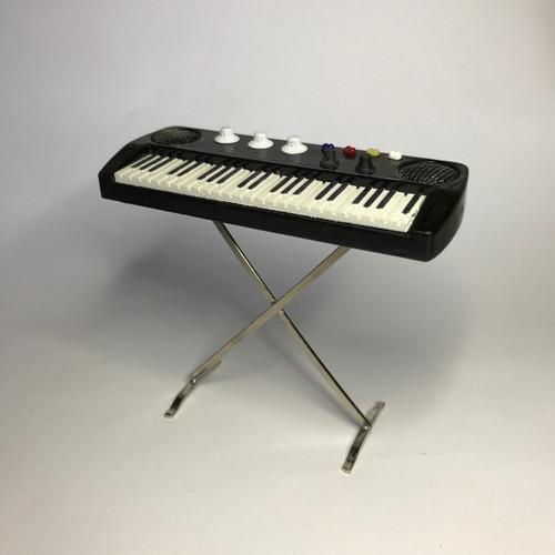 Electric keyboard/organ on metal stand.