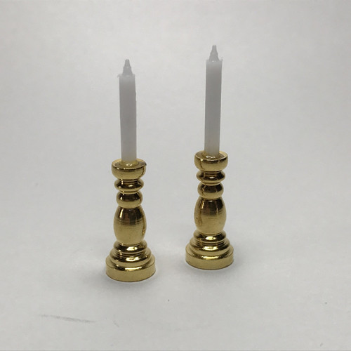 Pair of brass candlesticks with white taper candles