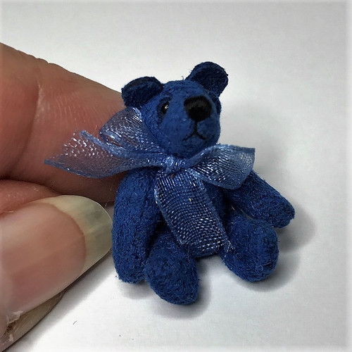 Lapis blue micro mini fully jointed bear shown seated with hand for scale