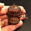 Miniature rusted bird cage in hand