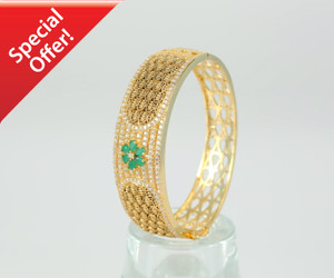 gold tone clasp bangle with beautiful flower design in emerald stones