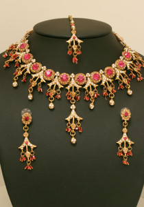 Designer fashion jewelry with magenta & clear stones set against gold background