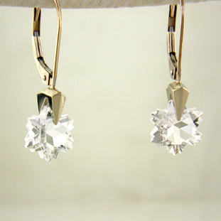What's better than one sparkling snowflake? Two, of course. One for each ear. And you can turn up the heat, because these snowflakes won't melt. Exclusively ours, each colorless topaz snowflake is custom cut just for us, in Canada, by master gem cutters. Each snowflake measures 8mm, and dangles in a 14 karat white gold Piercette® setting on a lever back, measuring 1 inch long.  Designed, and created in our studio by the artist Stuart J.  A Piercette® is a patented method of setting, with a gemstone that moves. The gem is set so that it swivels with every movement of the wearer, exhibiting extra sparkle.