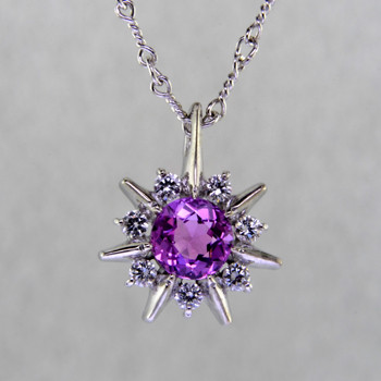 This beautiful pendant twinkles just like the stars at night. Our Starflake(tm) Sapphire and Diamond pendant is made in 14 karat White Gold, set with a mesmerizing 1.01ct. round Pink Sapphire, surrounded by .21ct. T.W. Ideal cut Diamonds. Includes a 14 karat White Gold twisted link chain, 18 inches long. Pendant measures 1/2 inch long.  Designed, and created in our studio by the artist Stuart J.
