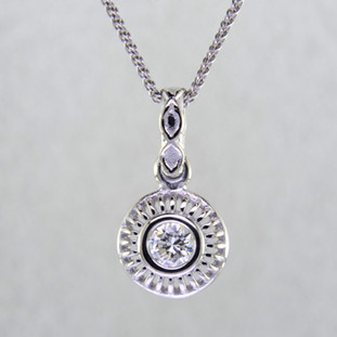 Blending traditional and modern for a timeless look, this diamond pendant dazzles day and night. Made in 14 karat White Gold, with a scintillating .24ct. Ideal cut Diamond. This beautiful diamond pendant hangs on a 14 karat White Gold 1.3mm cable chain, 18 inches long. Pendant measures 5/8 inch long.    Designed, and created in our studio by the artist Stuart J.