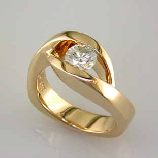 This elegant engagement ring has a low profile, and is easy to wear. Priced here in 14 karat gold for a 1/2ct. center (We can make it in any metal, and for any size diamond or colored gemstone). This is truly a timeless design, with no prongs to catch. Matching shadow wedding band is also available.  This custom designed engagement ring is individually crafted to be Perfectly You, and takes about 2 weeks to create. Call us for more information about how we can customize this design Just For You. Designed, and created in our studio by the artist Stuart J.
