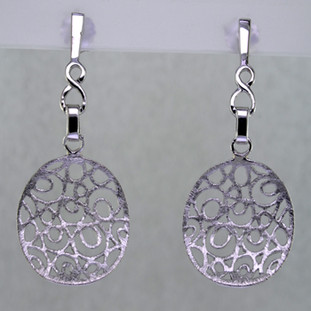 With an open lattice design, these light and airy earrings exude fun day or night. Easy to wear, and distinctively styled, they are handcrafted in durable rhodium plated Sterling Silver, dangling from posts. Measuring 1 1/2 inches long.  Handcrafted in Northern Spain.