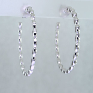 With just enough design to add a little spice, these hoops are perfect for everyday wear. Rhodium plated Sterling Silver. Measures 2 1/16 inches wide with posts.  Handcrafted in Northern Spain.
