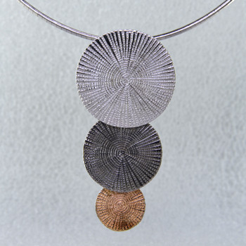 Feel a bit of Spanish flavor in this triple tier spiral pendant. Simple, sophisticated, and elegant. Ruthenium, rose gold, and rhodium plated sterling silver. Measures 1 3/4 inches long, and hangs on a 2mm round Sterling Silver omega wire, 18 inches long.  Handcrafted in Northern Spain.