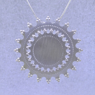 Playful and bright, this sunburst pendant is a delight to wear. Sterling Silver with a sunburst pattern and hangs on a 1.2mm Sterling Silver snake chain, 16 inches long. Pendant measures 1 1/2 inches long.  Handmade in Istanbul, Turkey.