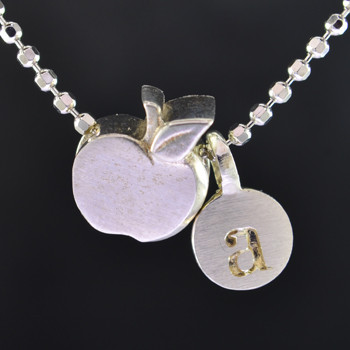 """What's your story? Begin with this Little Apple solid Sterling Silver charm. Wear it alone, with other charms (such as the Mini """"a"""" shown, and sold separately), or layered with other necklaces. Comes with a sterling silver ball chain, 16 inches long. The charm measures 1/4 inch long. Too cute!  Signified by a feminine sensibility and optimistic charm, Alex Woo's Little Icon Collections reinvent familiar symbols from the world around us into fresh and expressive designs.  Designed and handcrafted by Alex Woo in New York City."""