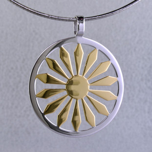 You can't help but feel sunny wearing this stylish pendant. A bold Yellow Gold plated sterling silver sunshine, encircled with a rhodium plated sterling silver border, that will bring a smile to your face. Includes a 2mm round Sterling Silver omega necklace, 18 inches long. Measures 1 3/4 inches in diameter. Hand-crafted by artisans in northern Spain.